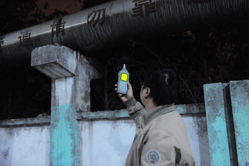 监测人员在夜间测试工厂噪音.