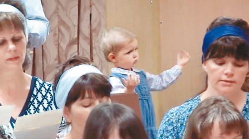可爱的金发小女童有个习惯,每当她跟爸爸妈妈上教堂的时候,一等到唱