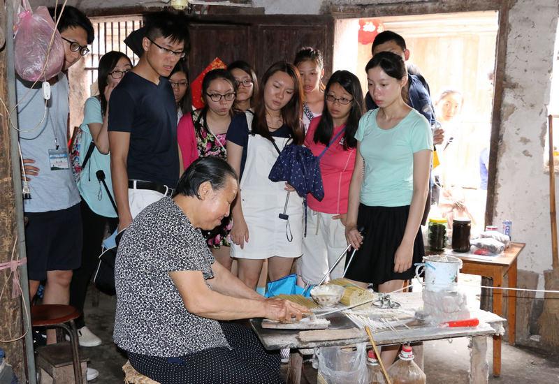 大学生们认真观看一位当地老奶奶手工制作烛芯.图片