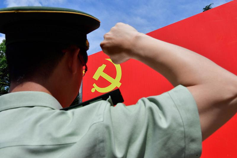 武警官兵手举右手,向着党旗重温入党誓词