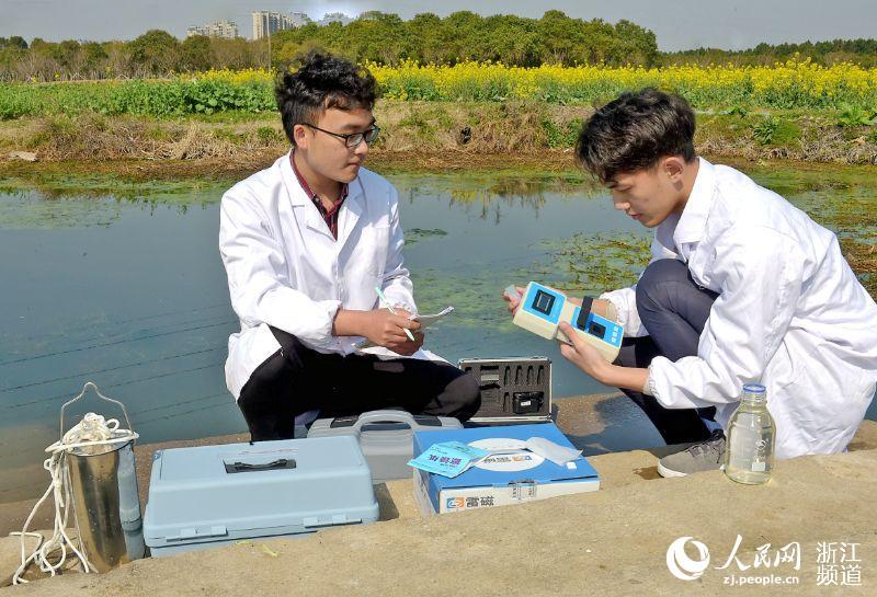"""大学生""""河长助理""""在永旺村测试水质氨氮含量。王国海 摄"""