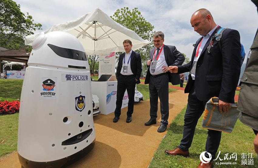 5月10日,来自波兰的客商在了解一款集各种安全保护功能为一体的的新型实用机器人。章勇涛 摄