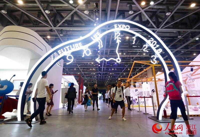 游客在未来生活节展馆前留影。江�h摄