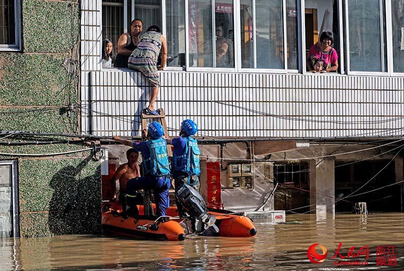 8月11日,浙江台州临海一救援队正在转移受灾群众。章勇涛 摄