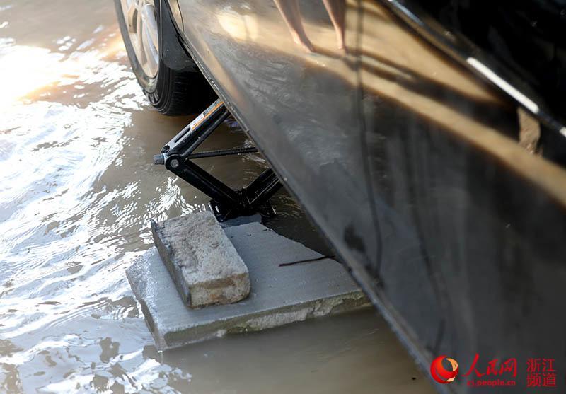8月11日,浙江台州临海一辆汽车用千斤顶支撑,防止被淹。章勇涛 摄