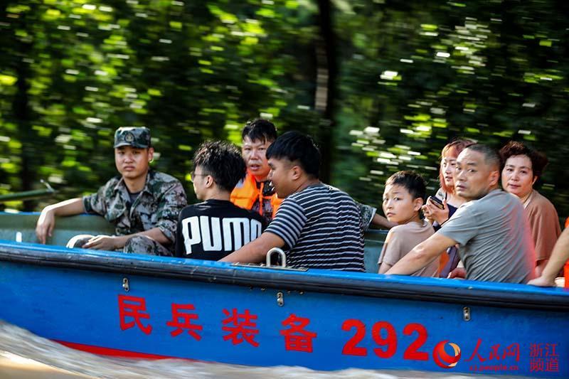 8月11日,浙江台州临海一民兵队伍正在转移受灾群众。章勇涛 摄