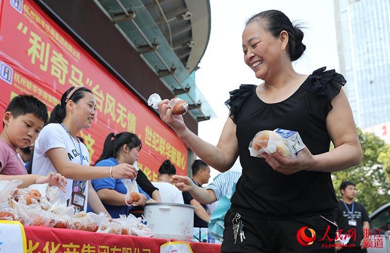 8月12日,市民领取物资。章勇涛 摄