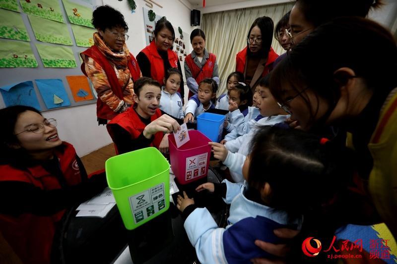 12月4日,在湖城仁皇山街道新时代文明实践所,来自美国的西席志愿者伍尔索恩正在与孩子们举办垃圾分类趣味互动。(吴建勋/摄)