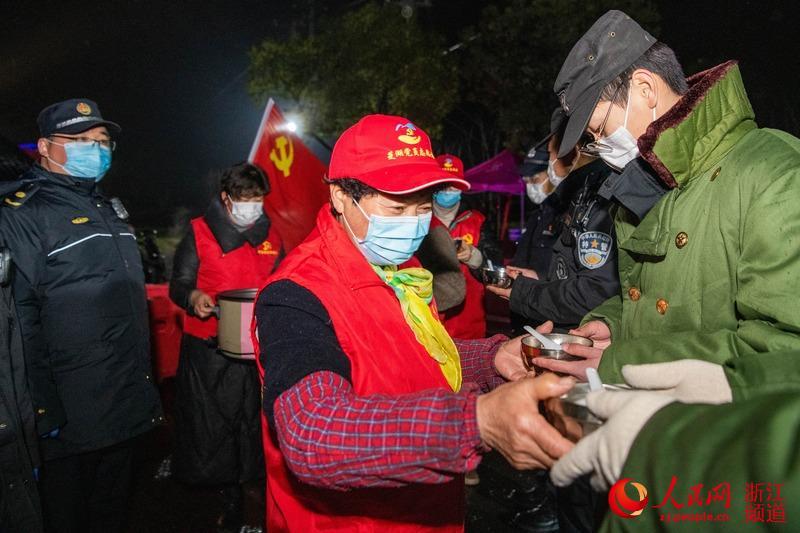 凌晨12点,浙江省湖州市南浔区菱湖镇的党员志愿者和工会志愿者们带着一锅热汤团,为卡点上值班的防疫一线的执勤民警送上元宵节的祝福。