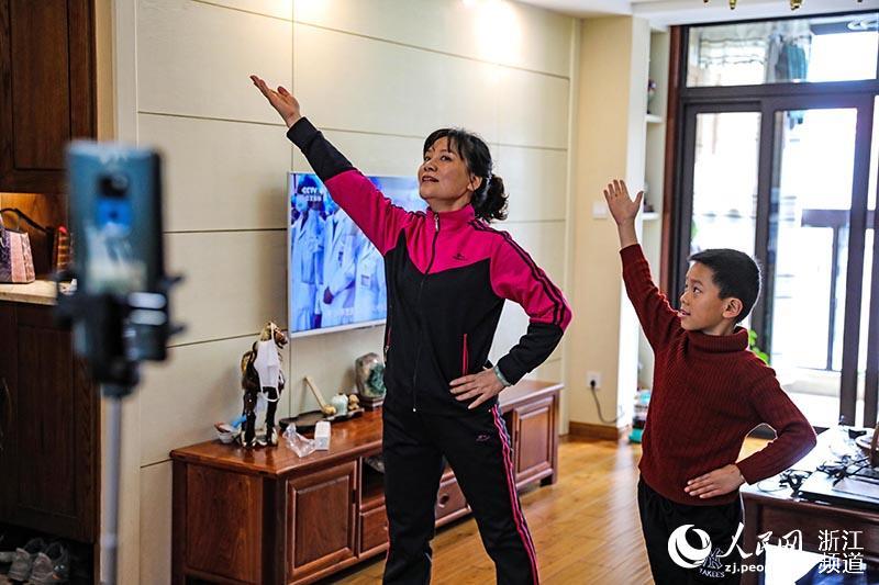 2月12日,在宁波市镇海区骆驼街道一小区, 箭港湖社区健身操队队长谢建明在家中打开音乐,通过网络连线与队员们同步做起操来。章勇涛 摄