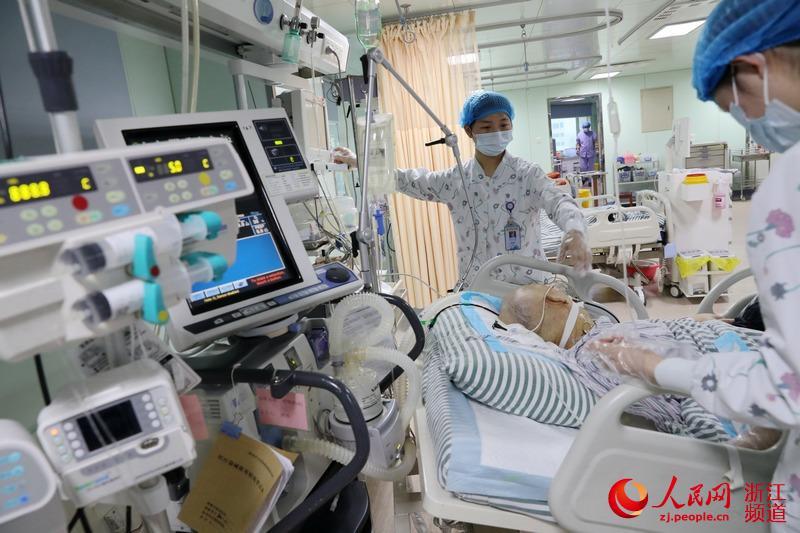 90后护士俞佳欣(前)和同事在进行护理工作。