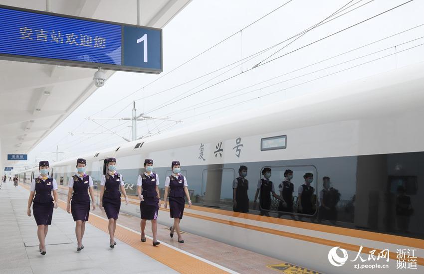 """高铁首次开进""""两山理论""""发源地安吉,乘务员们从列车旁经过。周围  摄"""